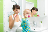 Mother with baby brushing teeth — Stock Photo