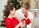 Young couple with gifts in front of Christmas tree at home — Foto de Stock