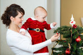 Mother and baby girl decorating Christmas tree at home — Stock Photo