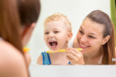 Mother teaching kid teeth brushing — Стоковое фото