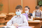 Pupils with protection mask against flu virus at lesson — Stock Photo