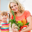 Mother and kid holding a shopping bag full of vegetables  on kit — Stock Photo