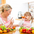 Mother and her child preparing healthy food and having fun — Stock Photo