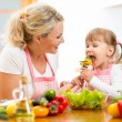 Mother feeding kid daughter vegetables in kitchen — Stock Photo