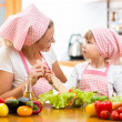 Mother teaching kid daughter mixing salad at kitchen — Stock Photo