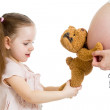 Kid girl and pregnant mother's stomach — Stock Photo