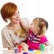 Kid girl and mother playing colorful clay toy — Stock Photo #33309619