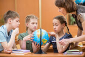 School kids studying a globe together with teacher — Stock Photo