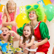 Stock Photo: Jolly children with clown on birthday party