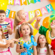 Jolly kids group with clown celebrating birthday party — Stock Photo