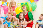 Jolly children with clown on birthday party — Stock Photo