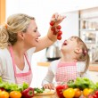 Mother preparing dinner and feeding kid  tomato in kitchen  — ストック写真