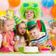 Kids with clown celebrating birthday party and blowing candles o — Stock Photo #34057609