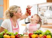 Mother preparing dinner and feeding kid tomato in kitchen — Stock Photo