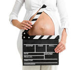 Pregnant woman hands holding clapper board on her belly — Foto Stock
