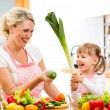 Mother and kid preparing healthy food and having fun — Stock Photo