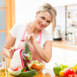 Cute woman cutting vegetables with device at the kitchen table  — Stock Photo