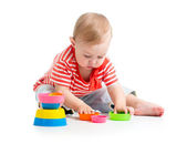 Funny little child is playing with toys while sitting on floor, — Foto Stock