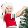 Foto Stock: Child girl decorating Christmas tree isolated on white