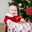 Kid girl dressed as Santa Claus in front of Christmas tree with — Foto Stock