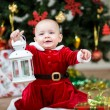 Baby girl dressed as Santa Claus at Christmas tree with lamp — Stock Photo