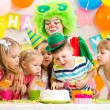 Children with clown celebrating birthday party and blowing candl — Stock Photo