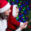 Baby girl with mother decorating Christmas tree on bright backgr — Stock Photo