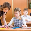 School kids work at labour lesson. Teacher helping pupil. — Stock Photo