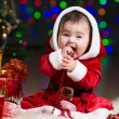 Kid girl dressed as Santa Claus at Christmas tree with gifts — Lizenzfreies Foto