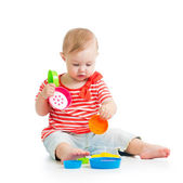 Funny little child is playing with toys while sitting on floor, — Stok fotoğraf