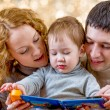 Family at christmas tree. Parents read book to kid. — Stock Photo