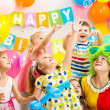 Jolly kids group with clown celebrating birthday party — ストック写真