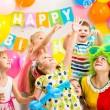 Jolly kids group with clown celebrating birthday party — Stockfoto