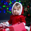 Kid girl dressed as Santa Claus at Christmas tree with gifts — Stock Photo