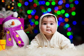 Smiling baby girl over Christmas background — Stockfoto