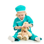 Doctor kid playing and curing toy isolated on white — ストック写真