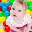 Top view of baby girl playing with colorful balls — Stock fotografie