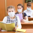 School kids with protection mask against flu virus at lesson — Stock Photo #36779615