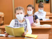 School kids with protection mask against flu virus at lesson — ストック写真