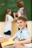 School kid in classroom at lesson — Stock Photo