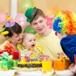 Baby girl celebrating first birthday with parents and clown — Stock Photo #36871131