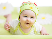 Smiling baby lying on green — Stock Photo