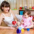 Kid girl and mother playing together with cup toys — Stock Photo #37154859