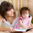 Stock Photo: Mom and kid read a book
