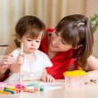 Cute mother and child painting together — Stock Photo