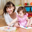 Mother and child play mosaic toy together indoors — Stock Photo #37240265