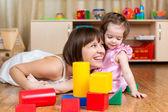 Hijo y madre alegre jugarcon con juguetes en piso — Foto de Stock