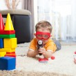 Kid playing with building blocks and imagining himself a hero — Stock Photo #38000115
