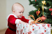 Baby in front of Christmas tree with big gift box — Stock Photo