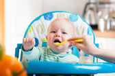 Mother feeding capricious baby with a spoon — Stock Photo
